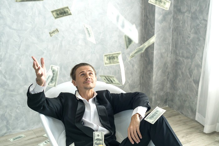 Suited man in bathtub throwing money into the air.