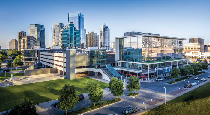 Retail center and parking facility with Houston Galleria skyline behind.