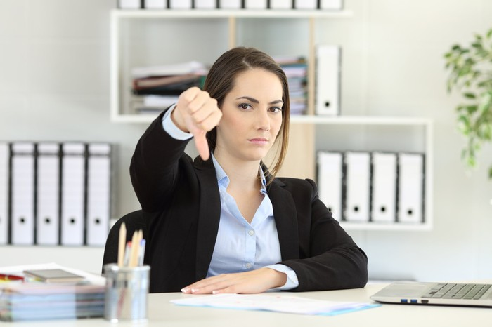 Woman in professional attire at desk making thumbs down sign