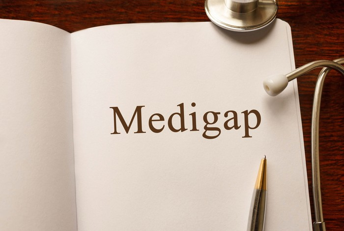 Notebook open to a page that says Medigap, with a pen resting on it