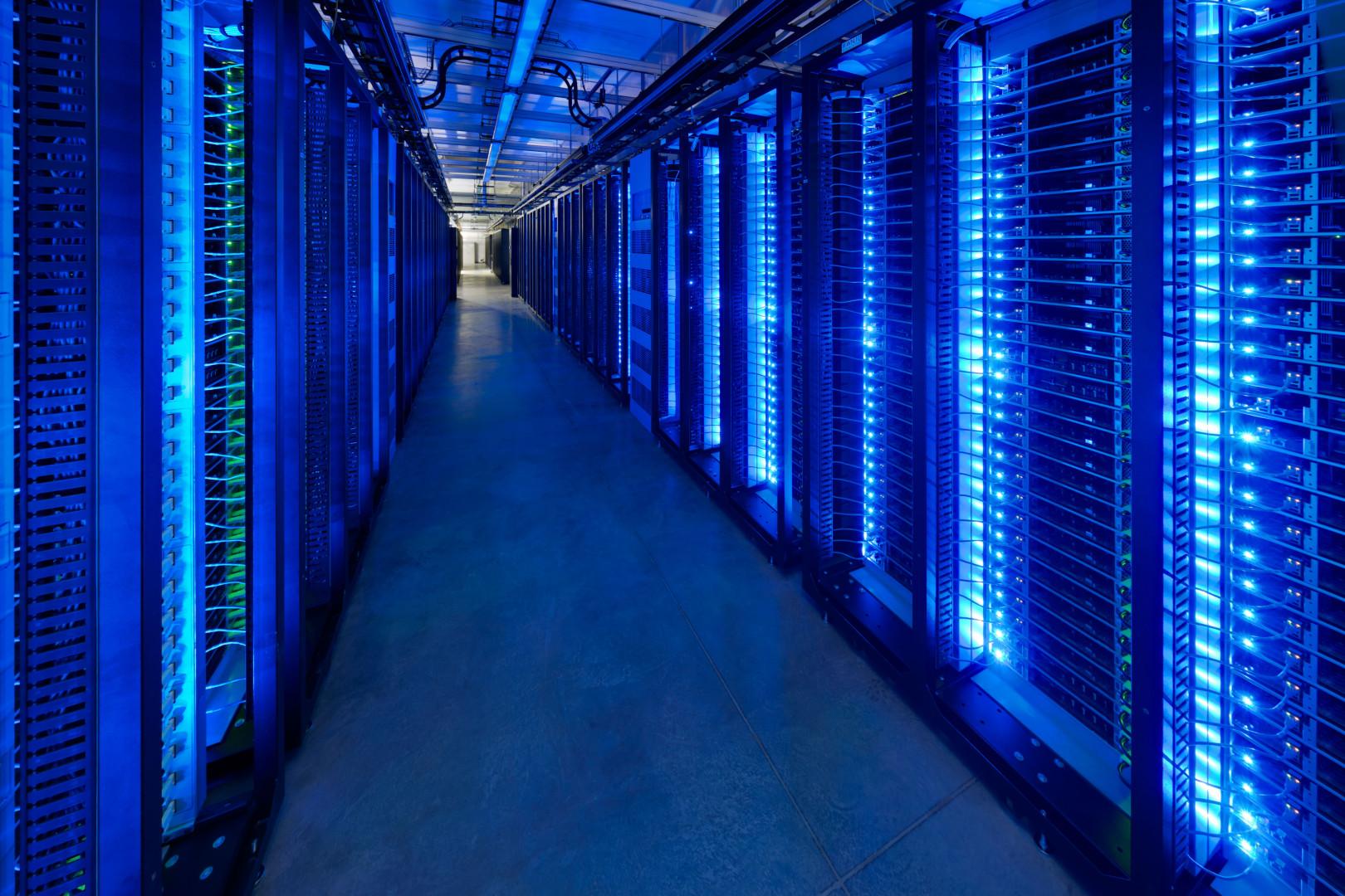 Dark data center room with blue glowing server lights.