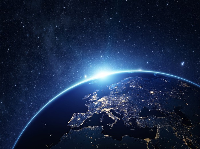 An image of earth at night. The European continent is in focus, lit up by night lights.