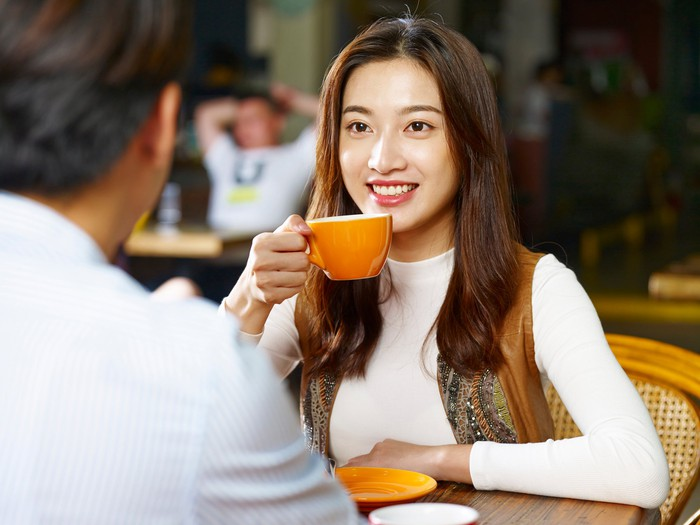 A young woman drinks coffee at a cafe.