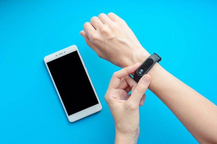 Close-up shot of one hand adjusting a fitness tracker worn on the other wrist. Below the hands, a smartphone lies on a sky-blue surface.