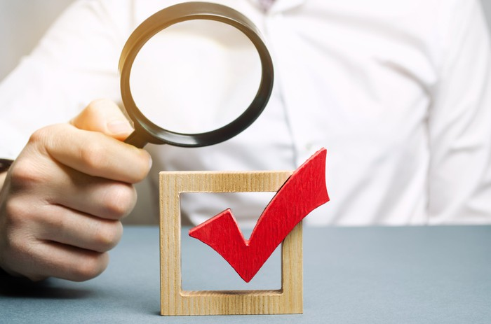 A person holding a magnifying glass above a wooden checkmark.