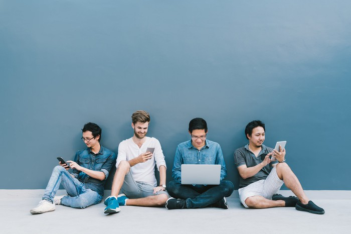 Four young men sitting on the floor using various electronic devices.