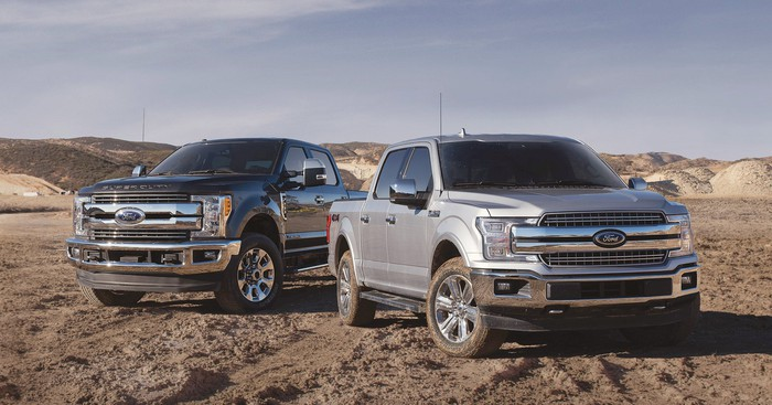 Two full-size Ford pickup trucks, a 2019 Super Duty and a 2019 F-150.