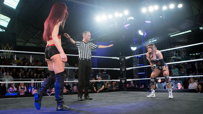 Two women wrestlers face off in the ring as a referee with hands outstretched stands between them.