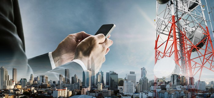 Superimposed over a city skyline, a red and white cell tower and a businessman using a smartphone.
