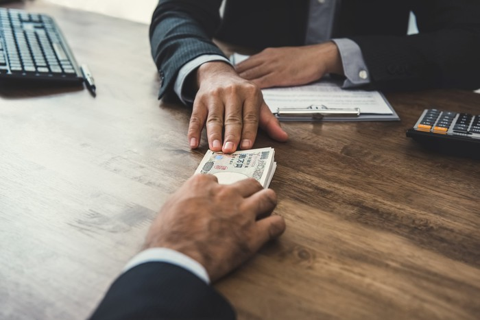 A hand passing money across a table.