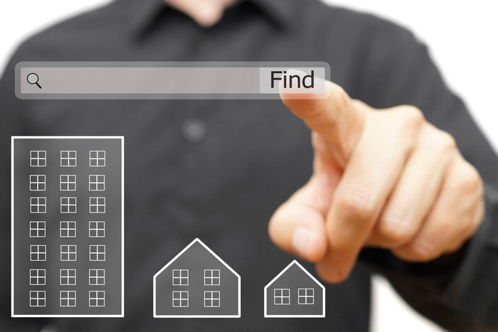 A person pointing to an internet search box above digital images of houses and an apartment building
