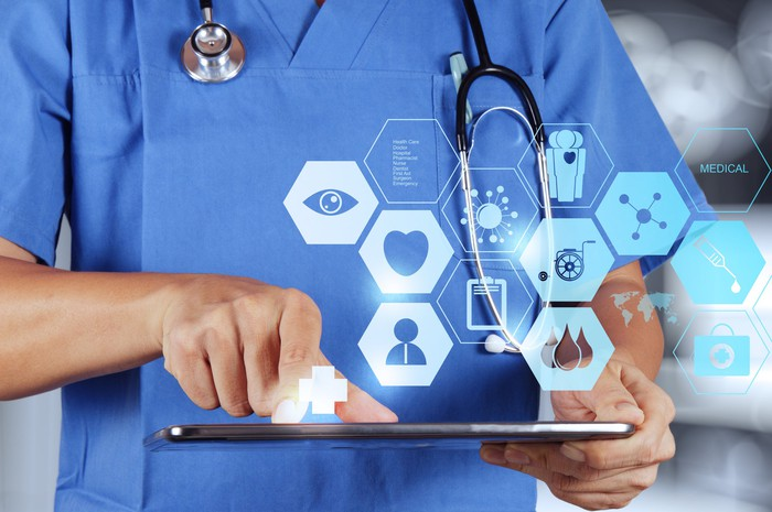 Doctor holding a tablet with healthcare icons appearing above the tablet