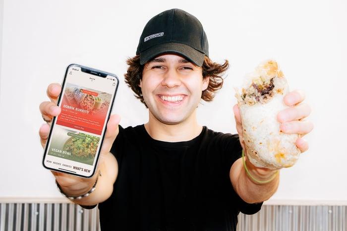 Person holding smartphone and Chipotle burrito.