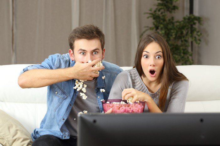 A young couple watching TV and sharing a bucket of popcorn by the handful on their couch. Woman has mouth open in surprise and man is stuffing popcorn in his mouth.