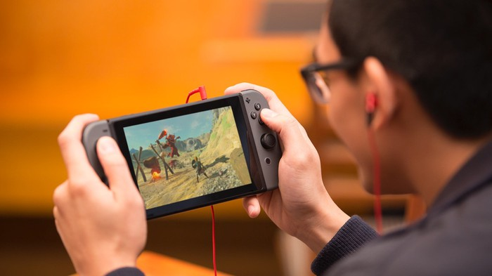 Man playing game on a Nintendo Switch with red ear buds plugged in