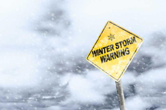 A winter storm warning sign in a snowstorm