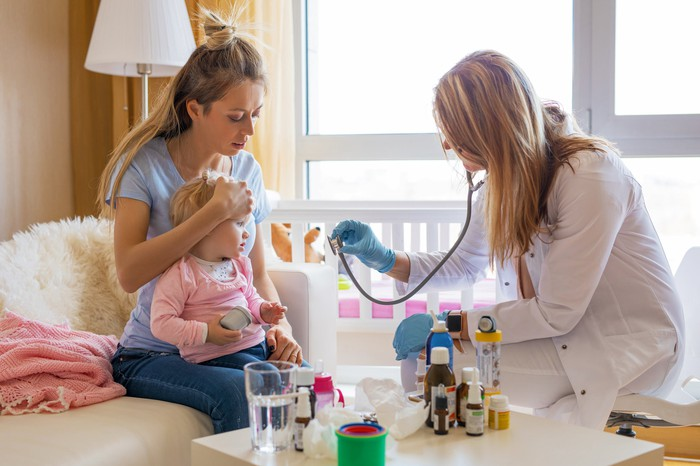 Home health nurse showing her stethoscope to a pediatric patient