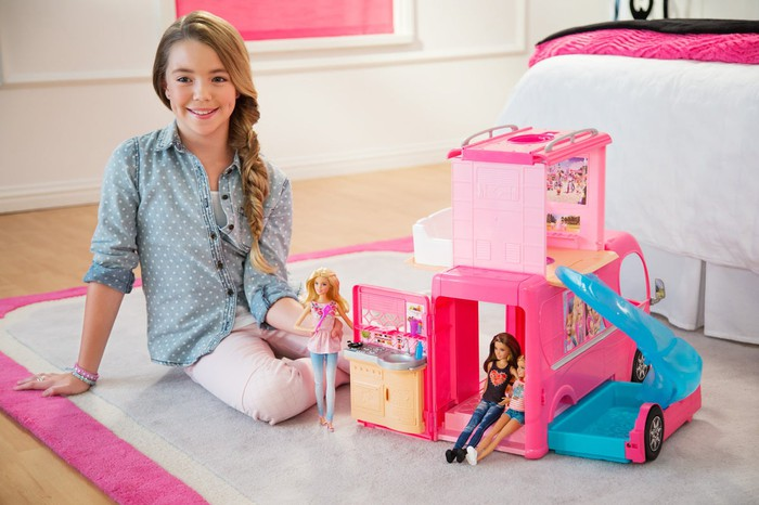 Young girl playing with Barbie dolls
