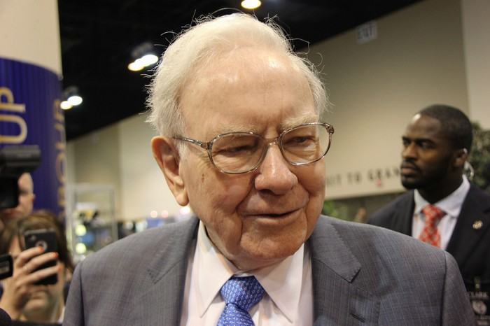 Warren Buffett speaking with a huddle of investors.