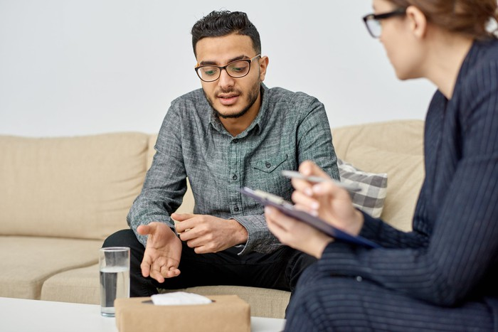 Psychiatrist talking to patient on a couch