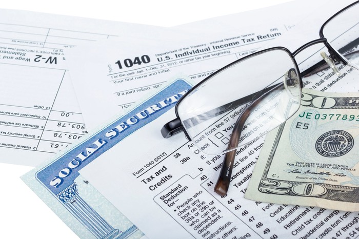 A Social Security card wedged between IRS tax forms, which are next to a pair of glasses and a 20-dollar bill.