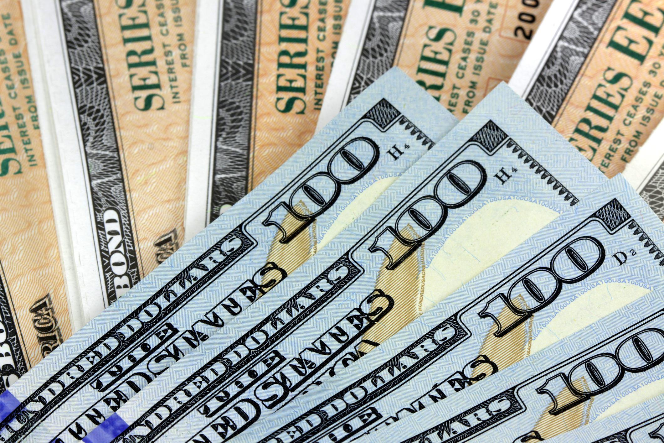 A fanned pile of crisp 100-dollar bills lying atop fanned Treasury bonds.
