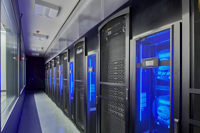 A data center with row after row of servers glowing blue.