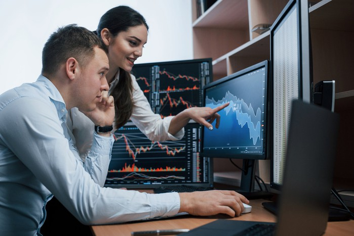 Two people look at a financial chart on a computer screen.