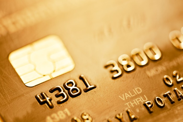 A close-up of a gold-colored credit card showing the EMV chip and part of the number.