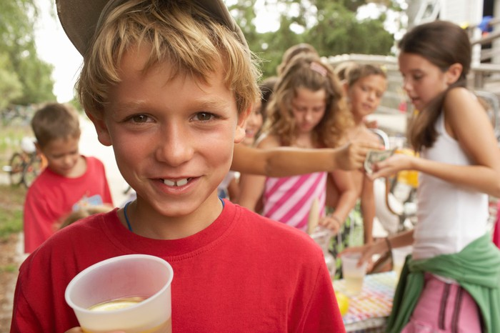 Boy smiling with lemonade stand in background