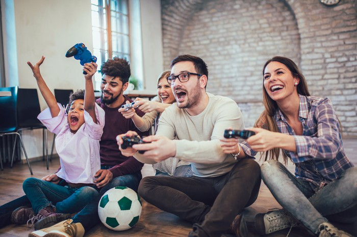 A family plays video games together sitting on the floor.