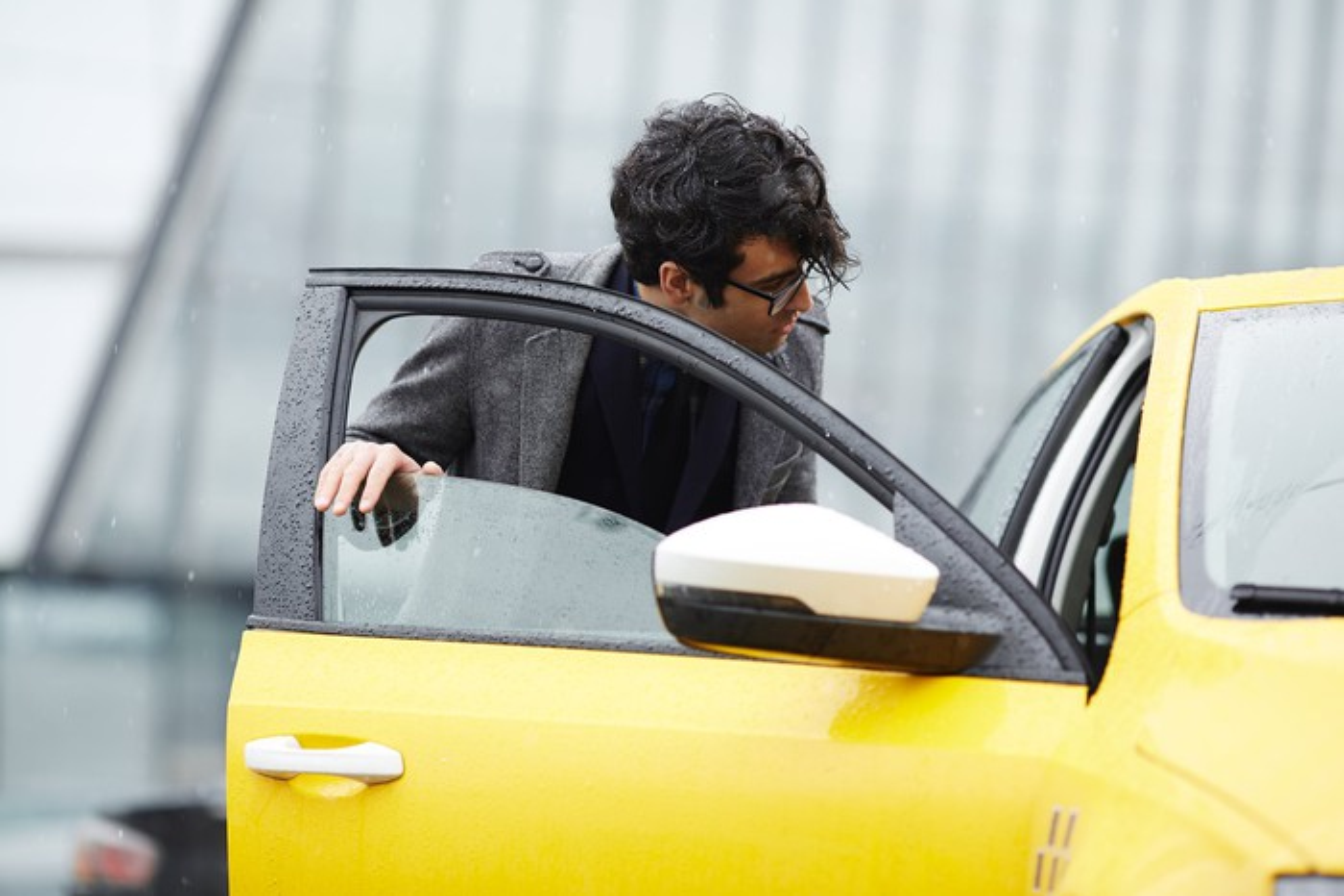 A man gets into a taxi.