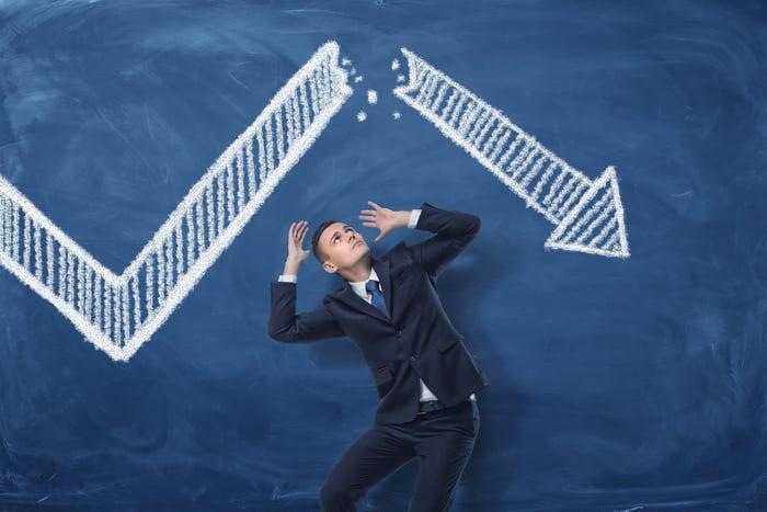 A businessman standing below a collapsing arrow.