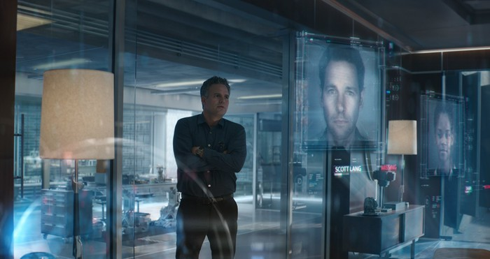 Mark Ruffalo as Bruce Banner stands in a lab with the faces of missing Avengers are projected on various digital screens.