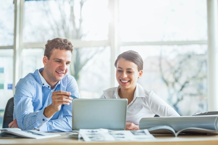 Professionally dressed man and woman at laptop, smiling