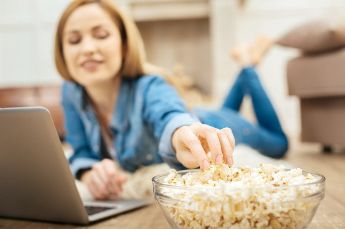 Woman eating popcorn on the floor while using a laptop.