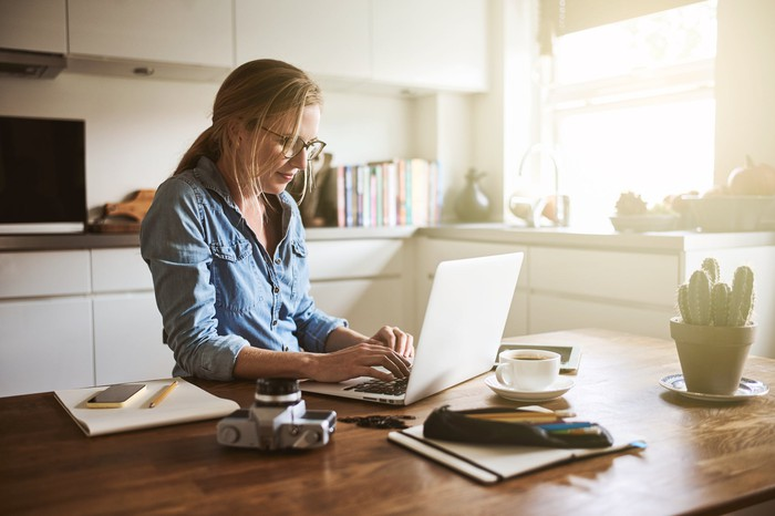 Woman typing on laptop in kitchen.