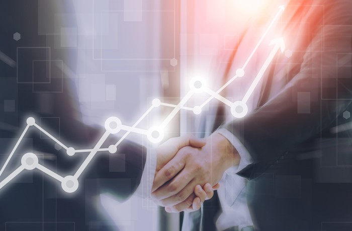 Businessmen shaking hands overlaid with arrows pointing upward.