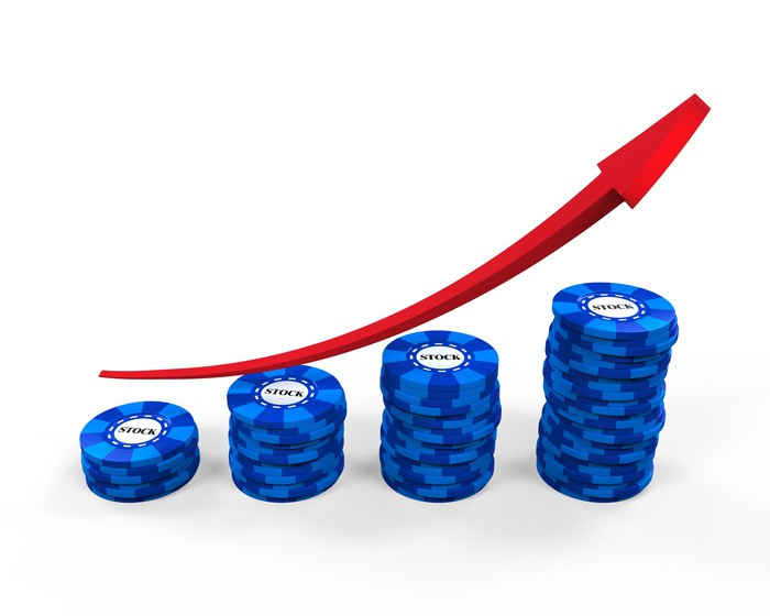 Red line trending up above stacks of blue poker chips with the word stock on them.