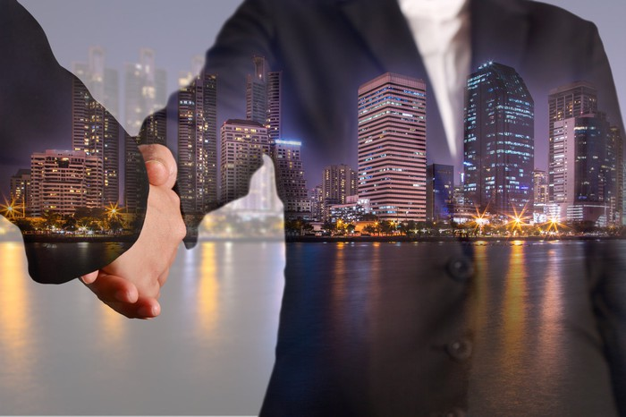 Two people shaking hands with a skyline of office building in the background.