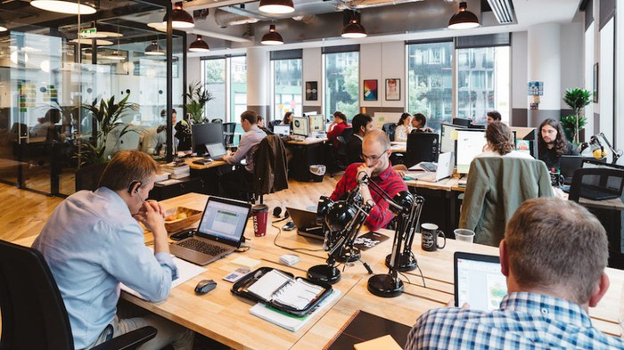 A WeWork workspace with professionally dressed men and women sitting at desks working on laptop computers.