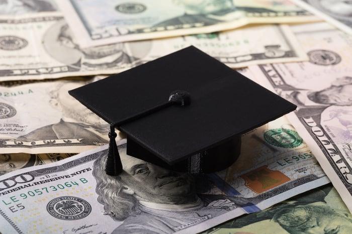 Graducation cap sitting on top of money