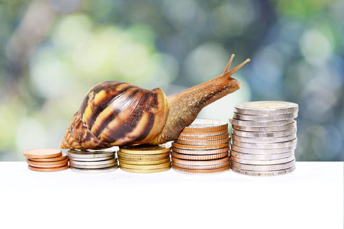 A snail climbing up ascending stacks of coins.