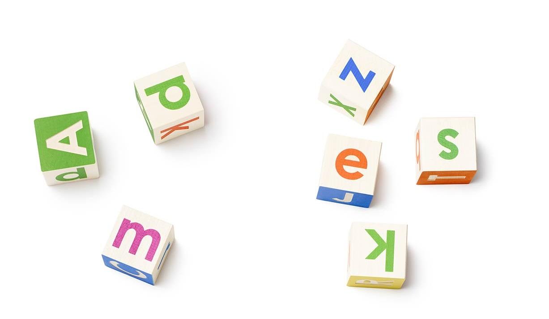 Seven alphabet blocks showing different-colored letters.