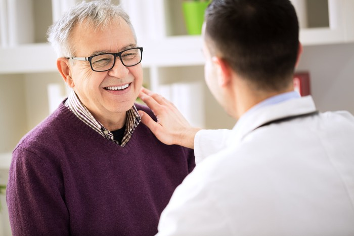 A young doctor touches an older man's shoulder.
