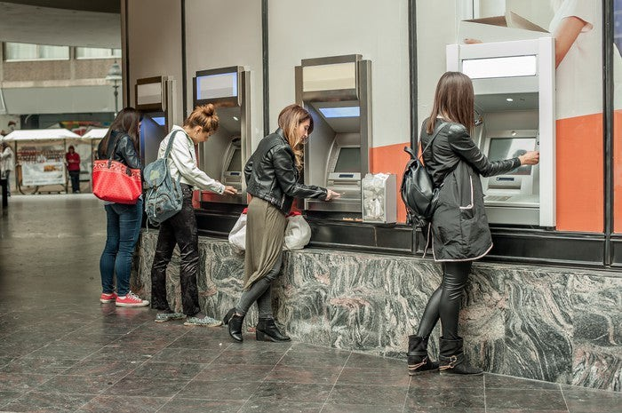 A line of customers withdrawing cash from a bank of ATMs