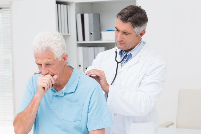 Older man covering mouth as if coughing while doctor listens through stethoscope pressed against his back