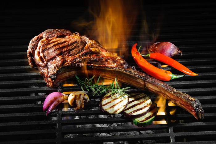 A steak and vegetables on a grill