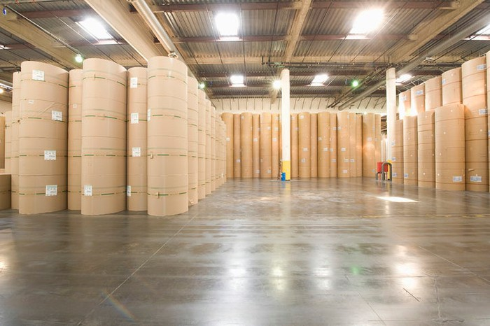 A warehouse storing large rolls of paper.