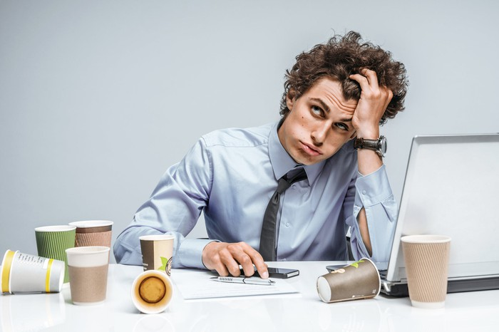 A professionally dressed man grabbing his hair as if stressed and sitting at a laptop computer with cups of coffee everywhere.